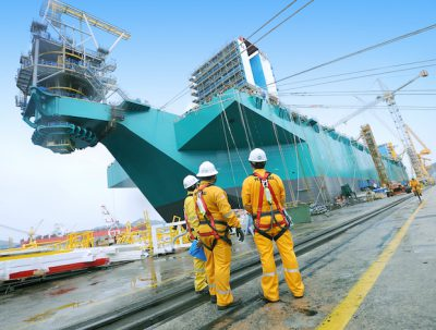 Petronas workers stand near the PFLNG, photo courtesy of Petronas