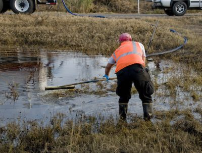A worker helps clean up an oil spill